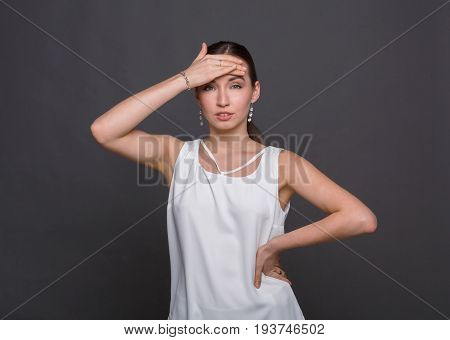 Attractive girl touches her forehead, might be she is sick. Young woman check her body temperature, healthcare and self-treatment concept