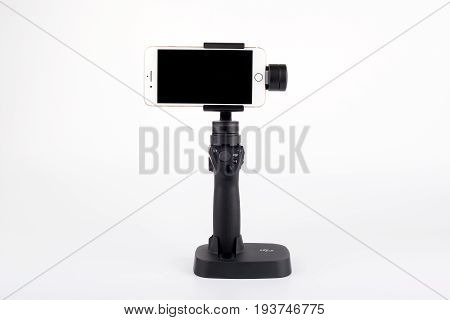 Riga, Latvia - July 3, 2017: New DJI Osmo Mobile gimbal stand for smartphone with Golden iPhone 7 Plus. The DJI Osmo hardware and mobile app allows smooth video shooting. 4k, Ultra HD