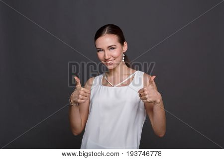 Happy young woman giving two thumbs up gesture. Smiling woman approve and recommend. Victory, luck, success concept