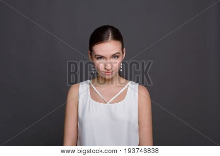 Portrait of serious woman looking straight. Confident female posing at camera, dark background