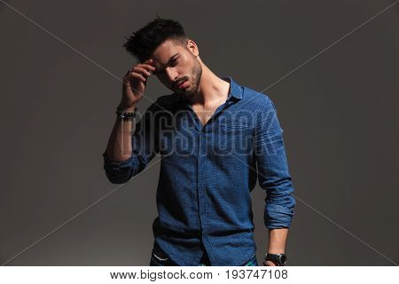 young pensive fashion man hold hand on forehead on grey background