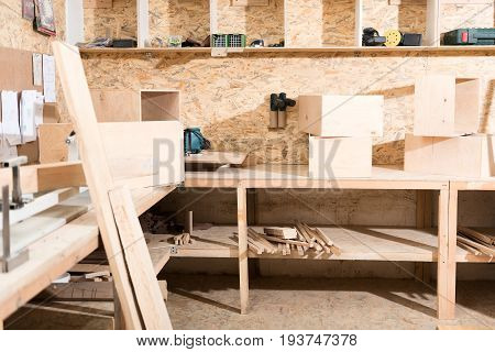 Workplace of carpenter with various wooden boxes, professional tools, planks and workbench on foreground