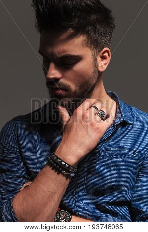 closeup picture of a pensive fashion man looking to side while holding his chin on thumbs on grey background