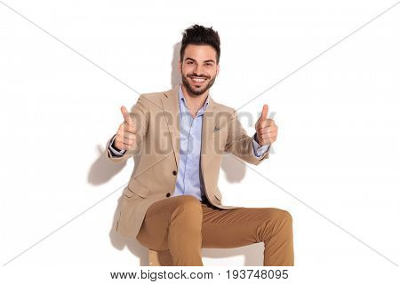laughing seated business man making the ok sign on white background