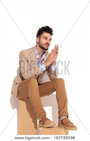 side view of a young businessman holding palms together and looks to side while sitting on white background