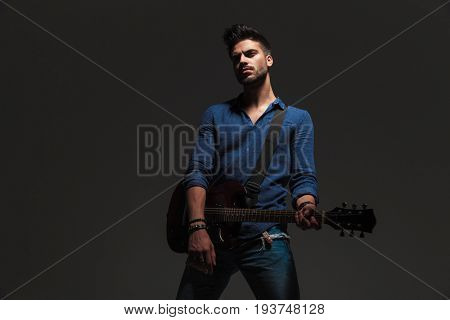 dramatic guitarist standing on grey background