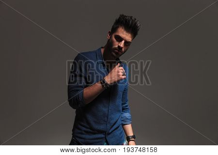 unshaved casual man posing in studio on grey background