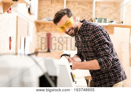 Favorite job. Cheerful bearded carpenter wearing safety glasses is laboring on lathe for wood. Shelves with professional equipment on background