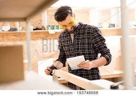 Verify design. Joyful young carpenter wearing safety glasses is standing near lathe for wood and checking sketch in his workshop