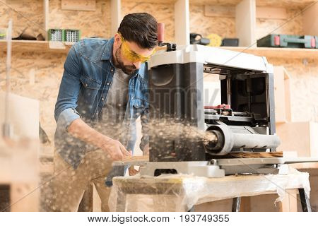 Make it good. Concentrated young carpenter wearing safety glasses is working on thickness planer equipped with hood. Focus on man