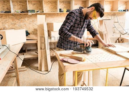 Happy at work. Positive young male carpenter in protective eyewear is using hand-held sander in his workshop with concentration. Copy space in the left side