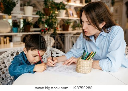 Mom and son drawing with colored pencils in a cozy room, shelves with flower pots on the backgrounds