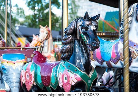 Beautiful horse Christmas carousel in a holiday park. Two horses on a traditional fairground vintage carousel. Merry-go-round with horses.