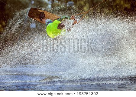 Man is among a splash of water he is riding a wakeboard an extreme athlete.