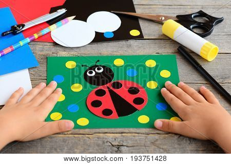Small child shows a ladybird card. Child made a card with ladybird. Stationery set on a desk. Preschool paper project. Developing children fine motor skills