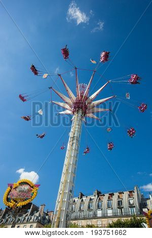 PARIS FRANCE - JULY 3 2017 : Parisians and tourists fly in the Parisian sky in one of the attractions of the fun fair installed in the Jardin des Tuileries in Paris during the summer 2017