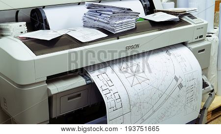 Jerusalem, Israel - May 21, 2017: Wide format printer is printing design draft outline sketch drawing in the printing house. Design office supply equipment.