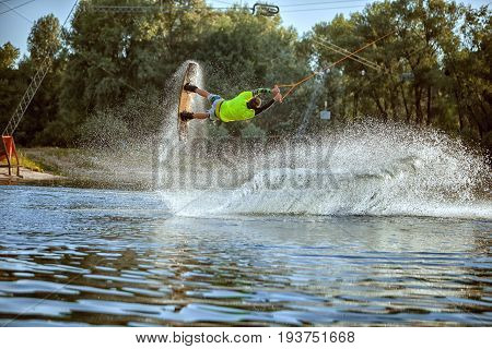 Wakeboarder young athlete he jumped over the water creating a splash.