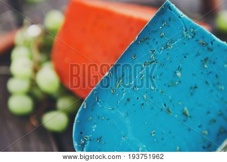 Gouda pesto violet and red cheese closeup. Blue and red cheese and grapes on rustic wood background, closeup, copy space