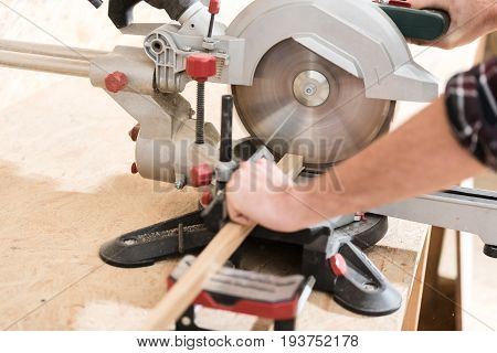 Professional equipment. Close-up of hands of skilled carpenter, which is cutting wooden plank using radial arm saw in his workshop
