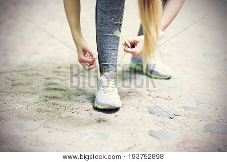Woman jogging in the forest and tying shoe