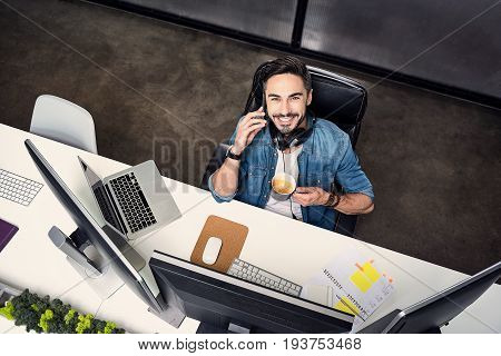 Joyful male freelancer is speaking on smartphone. He holding cup of coffee and looking up at camera with bright smile. Top view. Portrait