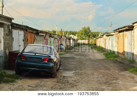 typical complex of old concrete garages with closed metallic doors in Russia. driveway road through garages with perspective and old blue parked car in summer day.