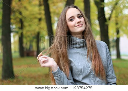 Beautiful young girl in leather jacket and black skirt standing and posing in autumn park. Pretty young woman with long straight brown hair