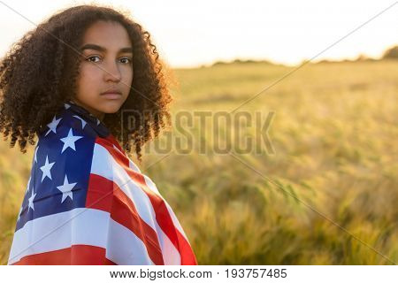 Sad depressed mixed race African American girl teenager female young woman with tears in her eyes in field of wheat or barley wrapped in USA stars and stripes flag in golden sunset evening sunshine