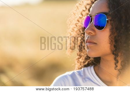 A beautiful and thoughtful mixed race African American female girl child teenager young woman in sunshine wearing blue reflective aviator sunglasses
