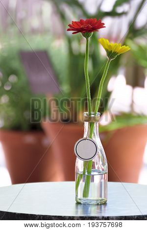 Floral table centerpiece with an empty label on a table. Empty copy space for Editor's text.