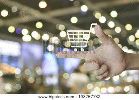 Shopping cart icon on finger over blur light and shadow of shopping mall Shop online concept