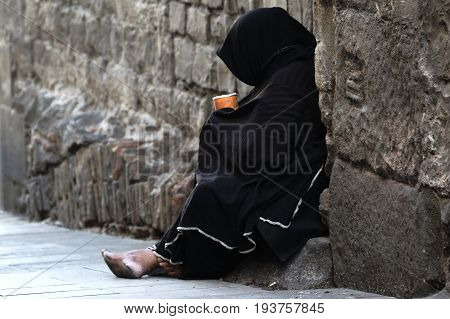 Poor woman begging sitting in the street. Empty copy space for Editor's text.