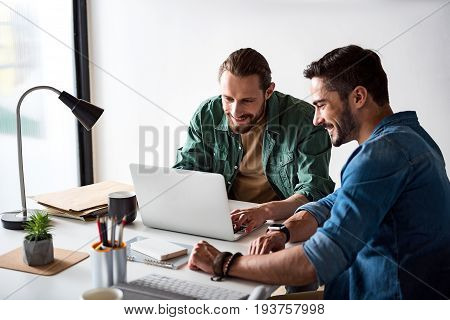 Happy man is using computer for creating project. Colleague is sitting near him
