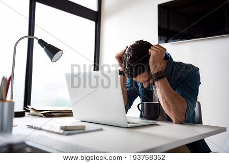 Disappointed freelancer is sitting near desk. Open laptop is on countertop afore despaired worker