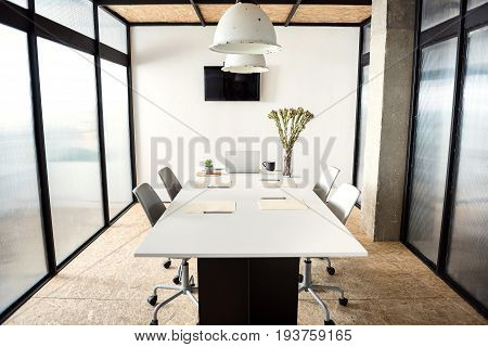 Modern laptop is on table near flowers in vase. Four chairs are around working desk in light office. Television set at wall