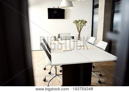 Comfortable chairs are around ascetic table in light room. Television set is at white wall