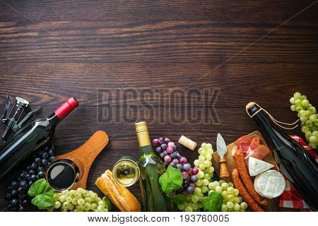 Wine bottles with grapes, cheese, ham and corks on wooden background with copy space