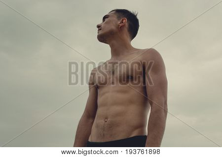 Muscular Man Standing On The Beach In A Speedo. The Concept Of Freedom, Power, Sport, Healthy Lifest