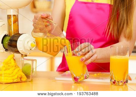 Woman young housewife in kitchen making fresh orange juice in juicer machine pouring drink from jug in glass. Healthy eating vegetarian food dieting and people