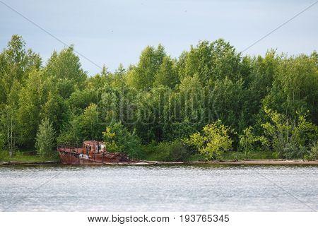 Old rusty sunken ship in water on coat
