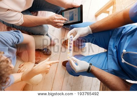My recommendation. Competent doctor holding weekly organizer for medicine in both hands while giving it to his teenager patient that being on the consultation at the moment