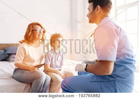 Happy mother. Competent doctor consulting his patient while sitting in semi position and being high spirited