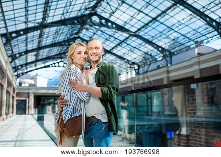 Portrait Of Smiling Couple Looking At Camera Hugging Each Other At Shopping Mall