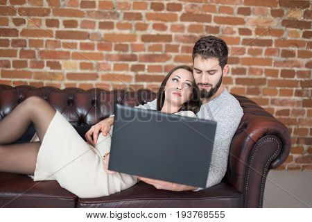 Young man watching up to man on sofa with laptop trust