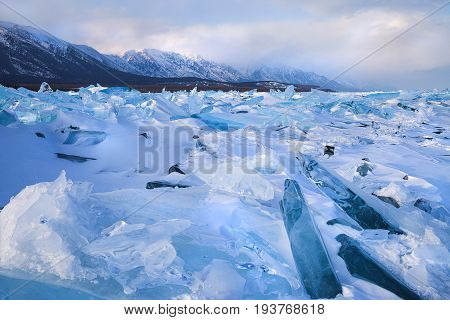 Snow and blue ice field along mountain range, winter landscape