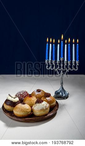 Hanukkah menorah candle holder for nine candles and sufganiyot - traditional donuts for Jewish holiday of Hanukkah