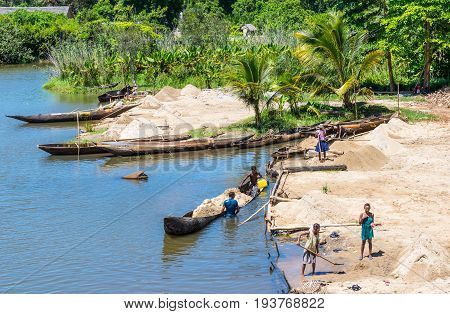 Ivoloina Madagascar - December 22 2015: Malagasy countryside people from the village unload sand from traditional handmade dugout wooden boats near the city of Toamasina (Tamatave) Madagascar East Africa. Everyday life on the river.