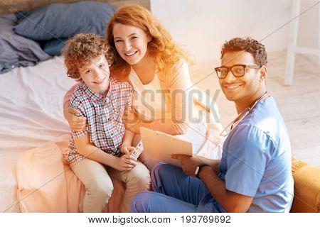 Happy people. Handsome medical worker keeping smile on his face and holding folder while sitting in semi position