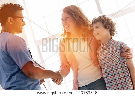 Hope not to see you soon. Competent doctor wearing glasses, standing in semi position while holding hands with patient